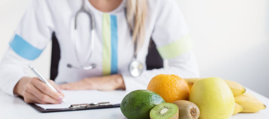 Dietitian doctor with healthy fruits on table